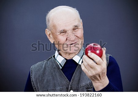 Closeup portrait happy, smiling , healthy, senior, elderly man holding, looking at apple, isolated, black, dark blue background. Human emotions, facial expressions, life perception good diet choices,  - stock photo