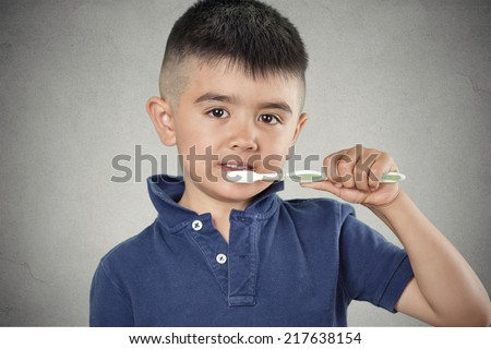 Closeup portrait happy, smiling little boy brushing his teeth with toothpaste, manual toothbrush isolated grey wall background. Oral dental health, disease prevention. Positive face expressions - stock photo