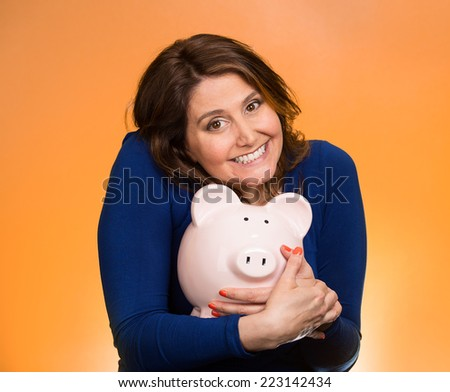 Closeup portrait happy smiling middle aged business woman holding piggy bank excited to save cash isolated orange background. Financial savings, banking concept. Positive emotion face expression - stock photo