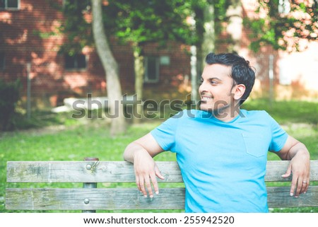 Closeup portrait, happy smiling, regular young man in blue shirt sitting on wooden bench, relaxed looking to side, isolate background trees, woods. Retro faded vintage look - stock photo