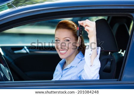Closeup portrait happy, smiling, young, attractive woman, buyer sitting in her new black car showing keys isolated city street dealership lot background. Personal transportation, auto purchase concept - stock photo