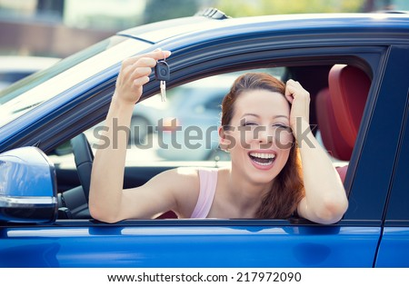Closeup portrait happy, smiling, young attractive woman, buyer sitting in her new blue car showing keys isolated outside dealer, dealership lot, office. Personal transportation, auto purchase concept - stock photo