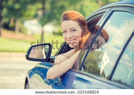 Closeup portrait happy smiling young attractive woman buyer sitting in her new car excited ready for trip isolated outside dealer dealership lot office. Personal transportation auto purchase concept - stock photo