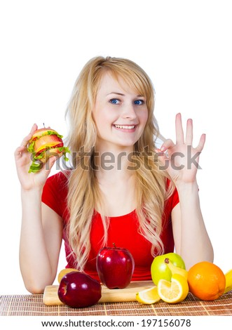Closeup portrait happy, smiling young, fit female holding, eating vitamin fruit sandwich, burger made of apples, oranges strawberries fruits giving ok sign isolated white background. Healthy lifestyle