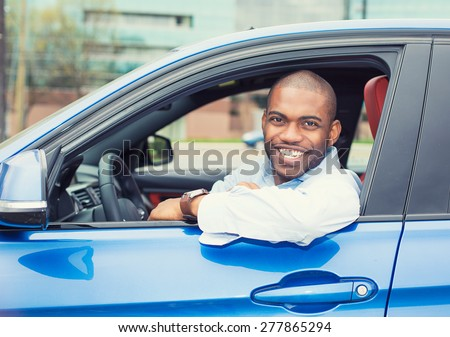 Closeup portrait happy smiling young man buyer sitting in his new car excited ready for trip isolated outside dealer dealership lot office. Personal transportation auto purchase concept - stock photo