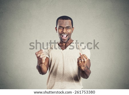 Closeup portrait happy successful young student man winning, fists pumped celebrating success isolated grey wall background. Positive human emotion, facial expression. Life perception, achievement - stock photo
