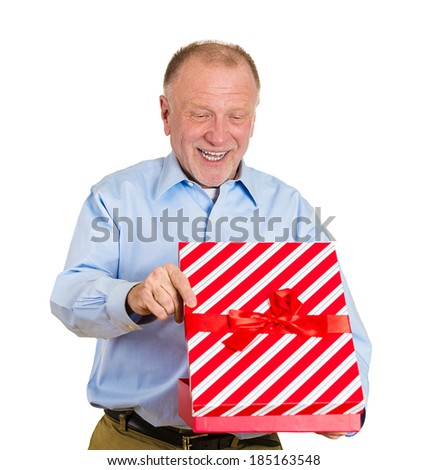 Closeup portrait, happy super excited senior mature man about to open unwrap red gift box isolated white background, enjoying his present. Positive human emotion facial expression feeling attitude - stock photo