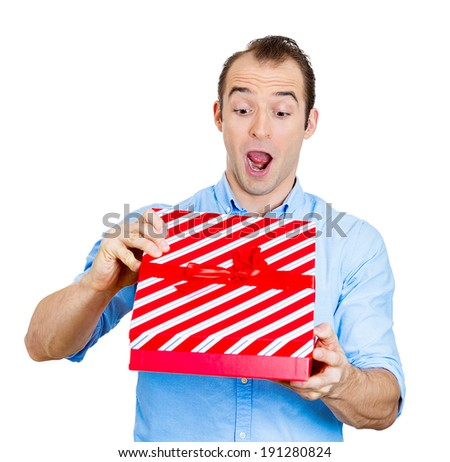 Closeup portrait happy, super excited, surprised young man about to open, unwrap red gift box isolated white background, enjoying his present. Positive human emotion facial expression feeling attitude - stock photo