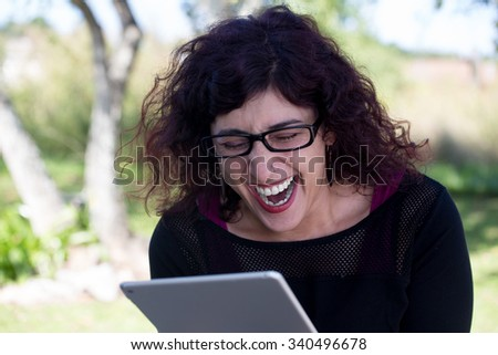Closeup portrait, happy woman in black shirt and glasses using silver pc, isolated outdoors background. Positive human emotion facial expressions feelings - stock photo