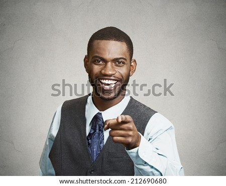 Closeup portrait happy young man, laughing, pointing with finger at someone, something, isolated grey wall background. Positive human face expressions emotion, feelings, attitude, approach, perception - stock photo