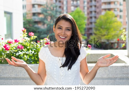 Closeup portrait, happy young pretty woman looking shocked surprised in disbelief, hands in air, open mouth, isolated buildings, flowers background. Positive emotion facial expression feeling attitude - stock photo