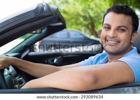 Closeup portrait, happy young smiling handsome man in blue polo shirt in his new black sports car, relaxing, looking at camera, isolated on outdoors background with vehicle and green trees. - stock photo