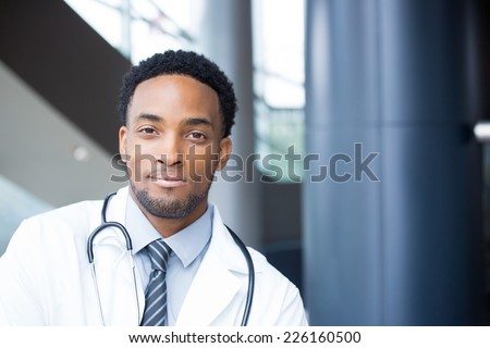 Closeup portrait head shot of friendly, smiling confident male doctor, healthcare professional with a white coat and stethoscope, looking at the camera, isolated hospital clinic background. - stock photo