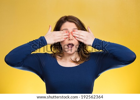 Closeup portrait, head shot young, coy woman, female closing eyes with hands can't see, hiding, mouth open, isolated yellow background. See no evil concept. Negative emotion, facial expression feeling - stock photo