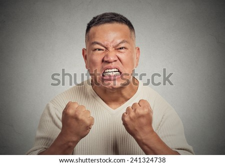 Closeup portrait headshot angry middle aged man with open mouth fist up in air aggressive screaming isolated grey wall background. Negative human emotion face expression feeling body language reaction