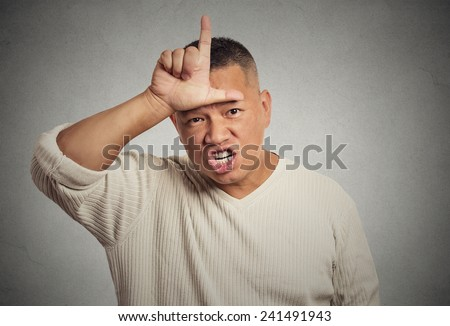 Closeup portrait headshot angry young man showing loser sign on forehead, looking at you with disgust at camera gesture, isolated grey wall background. Negative human emotion facial expression feeling