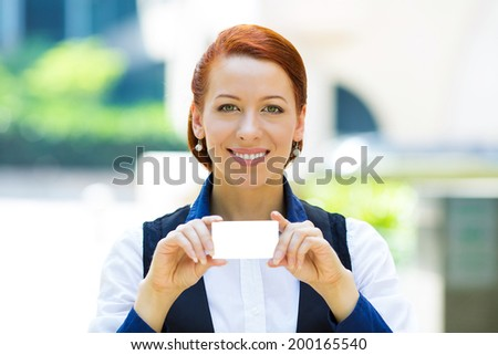 Closeup portrait, headshot attractive, happy, smiling businesswoman holding blank business card isolated city street background. Positive face expressions, emotions. Corporate bank employee agent  - stock photo