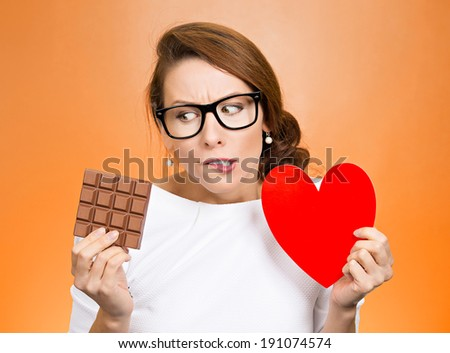 Closeup portrait, headshot beautiful, young nerd woman with black glasses holding heart craving square milk chocolate isolated orange background. Food diet option dilemma. Sweet temptation. Expression - stock photo