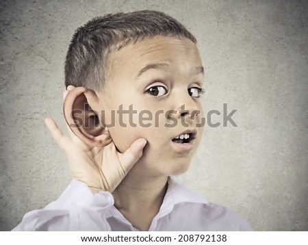 Closeup portrait, headshot boy, little man overhearing something, hand to big ear gesture, very curious, isolated grey, black background. Human face expression, emotion, body language, life perception - stock photo
