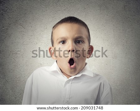 Closeup portrait headshot child with astonished face expression, opened mouth, isolated grey wall background. Human emotions, body language, perception. Unexpected discovery, reaction  - stock photo
