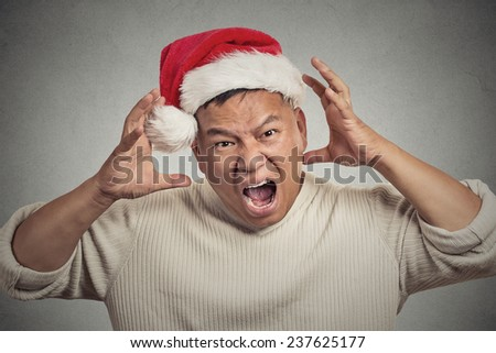 Closeup portrait headshot christmas man with red santa claus hat hands on head, stressed out, yelling, showing frustration. Negative human emotions face expression isolated on grey wall background