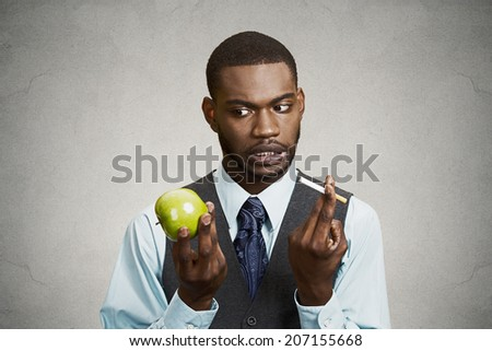 Closeup portrait headshot corporate executive businessman trying decide on healthy life choices, holding craving cigarette versus green apple isolated black background. Face expression body language - stock photo