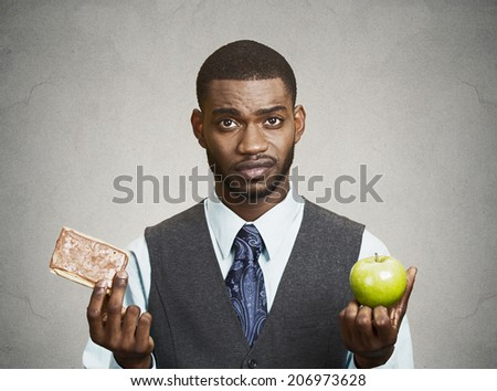 Closeup portrait headshot corporate executive, businessman trying to decide on diet, sweet cookie versus green fresh apple isolated black grey background. Weight control eating habits. Face expression - stock photo
