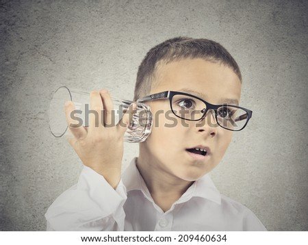 Closeup portrait, headshot curious nosy child using a glass as telephone listening to conversation, gossip, isolated grey wall background. Human face expressions, emotions, feelings, life perception - stock photo