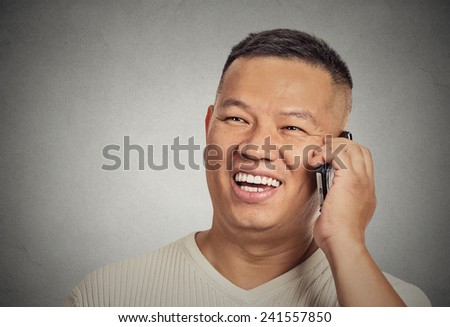 Closeup portrait headshot handsome young man student happy guy excited employee, using cell phone, smiling, having pleasant conversation isolated grey wall background. Human emotion face expression - stock photo