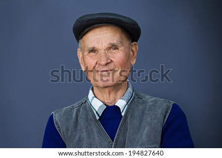 Closeup portrait, headshot happy, confident, cheerful, smiling, senior, mature man, grandfather with hat isolated blue background. Positive human emotions, facial expressions, feelings, attitude - stock photo