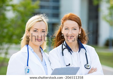 Closeup portrait headshot happy, smiling female doctors, healthcare professionals isolated outdoors hospital background. Patient visit. Health care reform. Positive human face expression, emotion - stock photo
