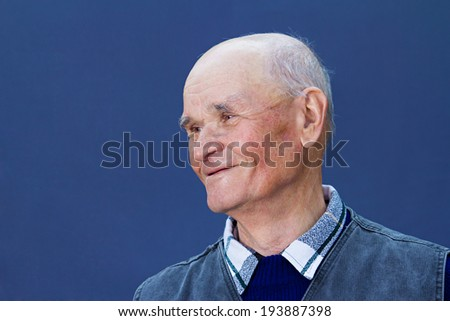 Closeup portrait, headshot happy, smiling mature, old man, grandpa isolated blue background. Positive human emotions, facial expressions, reaction, life perception, attitude - stock photo