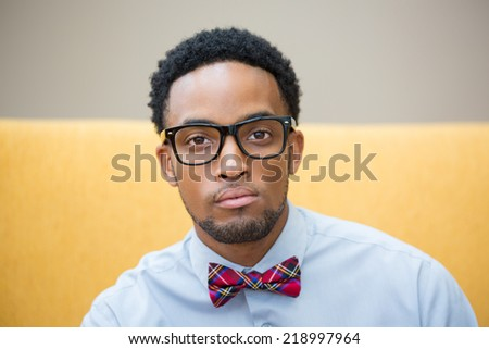 Closeup portrait headshot, high iq, intelligent guy with black glasses and bow tie, isolated yellow white background - stock photo