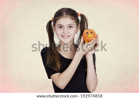 Closeup portrait, headshot, little, smiling, funny looking girl holding, saving money in piggybank, isolated black grey background. Positive facial expressions, emotions, clever financial decisions - stock photo