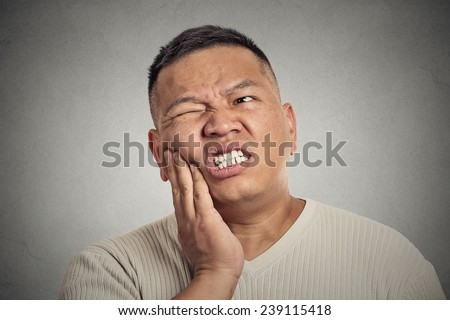 Closeup portrait headshot middle aged man touching face having bad pain, tooth ache, isolated grey wall background. Negative human emotions, facial expressions, feeling reaction. Health problems  - stock photo