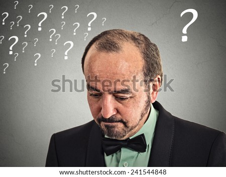 Closeup portrait headshot sad, depressed, desperate, alone, disappointed in life middle aged man looking down isolated grey wall background with question marks. Negative human emotion face expression - stock photo