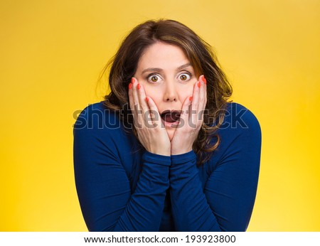 Closeup portrait, headshot startled woman, looking shocked, surprised, full disbelief, hands on face, isolated yellow background. Negative human emotion, facial expression, feeling, reaction disbelief - stock photo