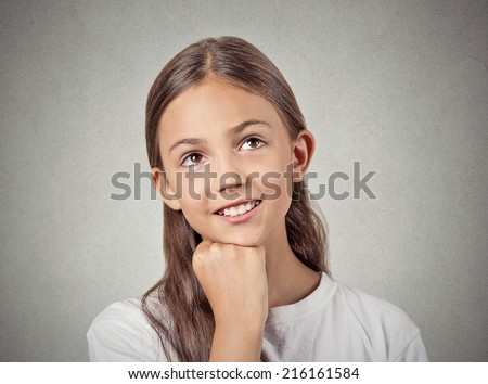 Closeup portrait, headshot thinking, daydreaming child, smiling girl, head on fist, looking up, isolated grey wall background. Positive human facial expression, emotions, feelings, life perception - stock photo