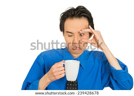 Closeup portrait headshot tired falling asleep young businessman holding cup of coffee, struggling not to crash stay awake, keeping his eyes opened, isolated white background. Lack of sleep concept