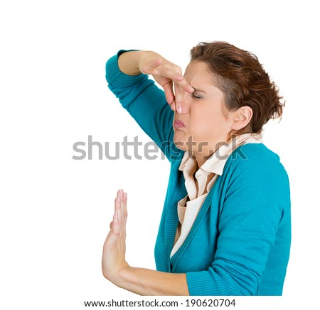 Closeup, portrait, headshot unhappy woman covers her nose, looks displeased, disgusted, something stinks, bad smell situation, isolated white background. Human facial expressions, emotions, reaction