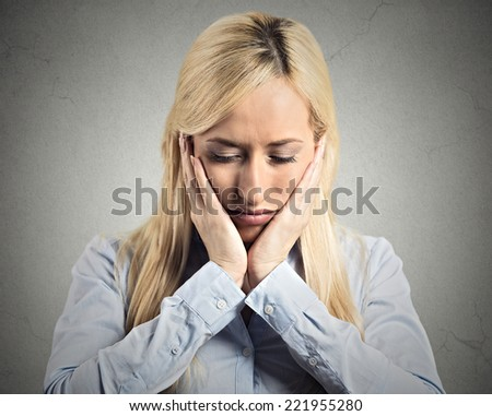 Closeup portrait headshot unhappy young business woman, hands on head bothered by mistakes having bad headache isolated grey wall background. Negative human emotion, facial expression feeling reaction