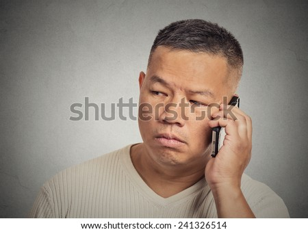Closeup portrait headshot upset, sad, depressed, worried young man employee father worker talking on mobile phone isolated grey wall background. Human face expressions, emotions, feelings, reactions - stock photo
