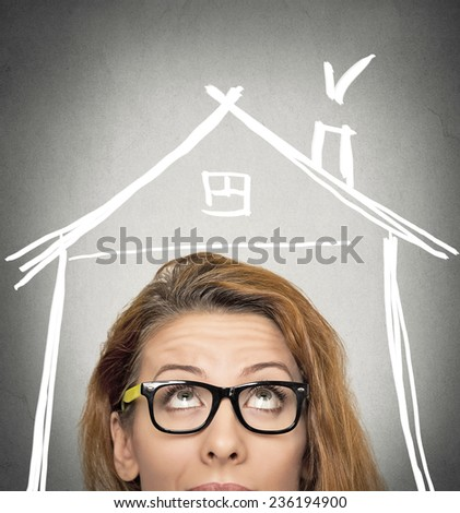 closeup portrait headshot woman looking up house roof above head isolated on grey wall background with copy space. Human face expression life perception. Security safety concept. Real estate market  - stock photo