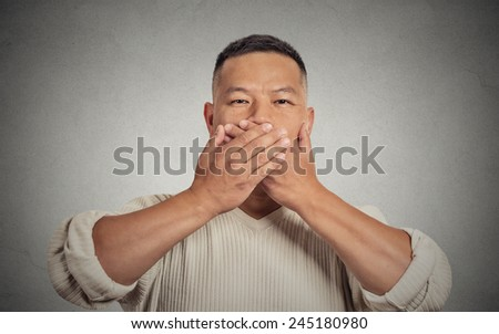 Closeup portrait headshot young man student worker employee covering his mouth with hands. Speak no evil concept isolated grey background. Human face expression feeling sign body language perception - stock photo