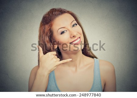 Closeup portrait headshot young single woman excited happy student making showing call me gesture sign with hand shaped like phone isolated grey wall background. Positive human emotion face expression - stock photo