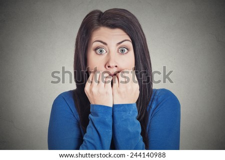 Closeup portrait headshot young unsure hesitant nervous woman biting her fingernails craving for something or anxious, isolated grey wall background. Negative human emotions facial expression feeling  - stock photo