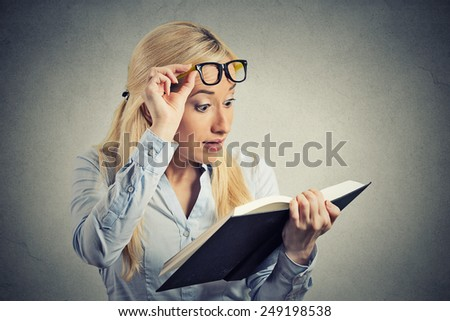 Closeup portrait headshot young woman wide opened eyes looking at book page shocked surprised by twists turn of story isolated grey wall background. Human emotion facial expression feeling reaction - stock photo