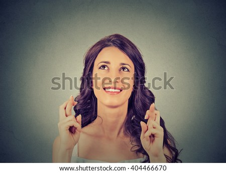 Closeup portrait hopeful beautiful woman crossing her fingers, hoping, asking for best looking up isolated on gray wall background. Human face expression, emotions, feeling attitude reaction - stock photo