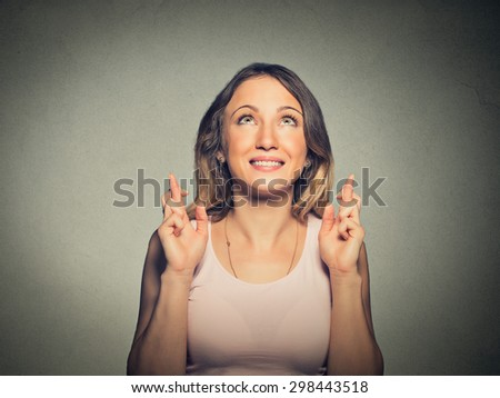 Closeup portrait hopeful beautiful woman crossing her fingers looking up hoping, asking best isolated on gray wall background. Human face expression, emotions, feeling attitude reaction - stock photo