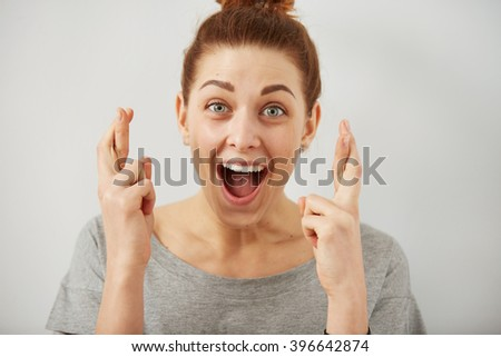 Closeup portrait hopeful beautiful woman crossing her fingers, open eyes, hoping, asking best isolated on gray wall background. Human face expression, emotions, feeling attitude reaction - stock photo